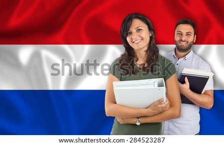 Couple of young students with books over Dutch flag - stock photo