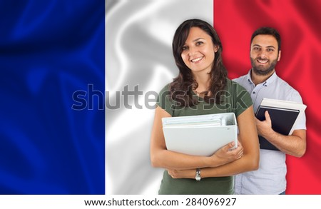 Couple of young students with books over french flag - stock photo