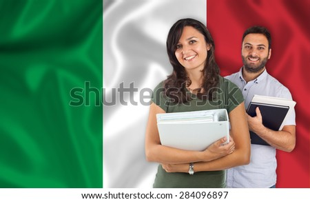 Couple of young students with books over italian flag - stock photo