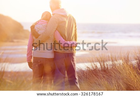 couple on a beach holding hands at sunset - stock photo