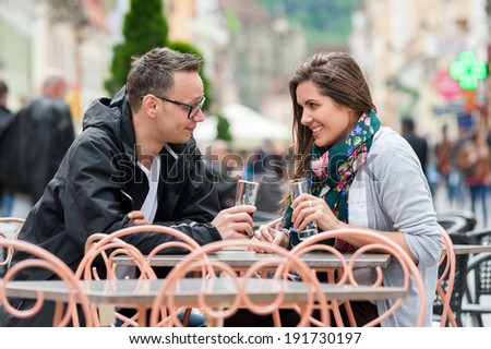 Couple on a coffee shop terrace drinking, talking, having fun laughing smiling happy. - stock photo