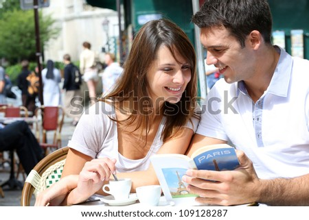 Couple on a coffee shop terrace reading tourist book - stock photo