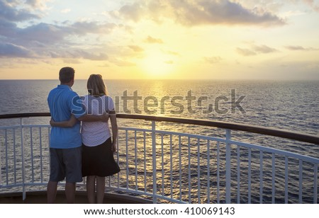 Couple on a cruise watching the sunset over the ocean - stock photo