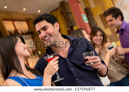Couple on a date at the bar having drinks - stock photo