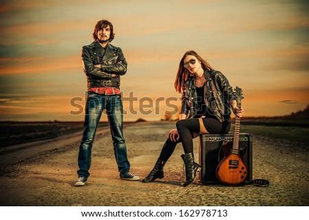 couple on a sunset road to horizon - stock photo