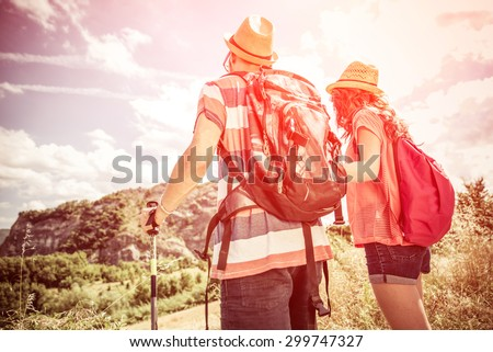 couple on a trekking excursion. they are watching their goal, the top of the mountain. concept about people,nature, leisure and sport - stock photo