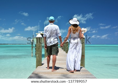 Couple on a wooden jetty. Exuma, Bahamas - stock photo