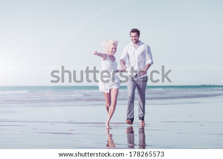 Couple on beach in white clothing running down on vacation or honeymoon - stock photo