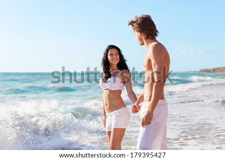 Couple on beach, love hold hands. Young happy man and woman sea shore smiling romantic looking each other, summer ocean vacation holiday blue sky - stock photo