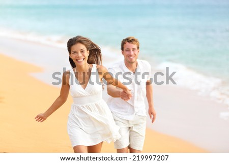 Couple on beach running having fun laughing in elegant casual beach wear. Happy multicultural multi-ethnic young lovers and friends by ocean on summer vacation holidays travel. Woman and man. - stock photo