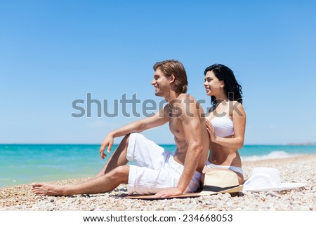 Couple on beach summer vacation, young man and woman embracing smile looking side to copy space, concept travel - stock photo