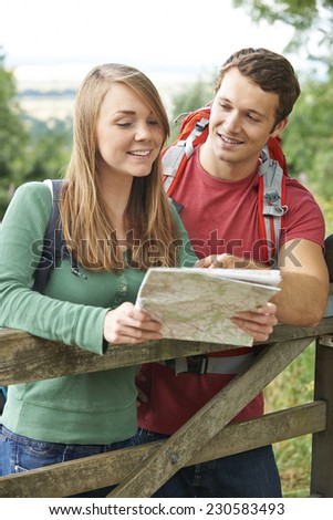 Couple On Hike Through Countryside Looking At Map - stock photo