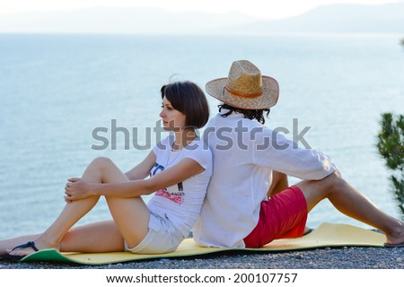 couple on holiday: young beautiful woman with man having fun sitting back to back on sea shore showing misunderstanding to each other & looking at blue outdoors copy space background portrait image - stock photo