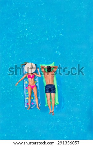 Couple on lilos Relaxing in a pool - stock photo