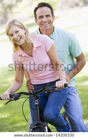 Couple on one bike outdoors smiling - stock photo