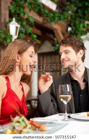 Couple on romantic date at a restaurant with food and wine - stock photo