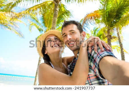 Couple on summer tropical vacation taking selfie photo on the beach. Man and woman on Mexico caribbean travel. - stock photo