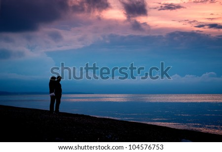 Couple on the beach at sunset and stormy clouds over the sea - stock photo