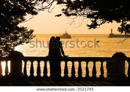 couple on the beach at yellow sunset (sunrise) - stock photo