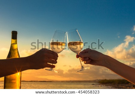 Couple on the beach celebrating with a glass of wine.  - stock photo