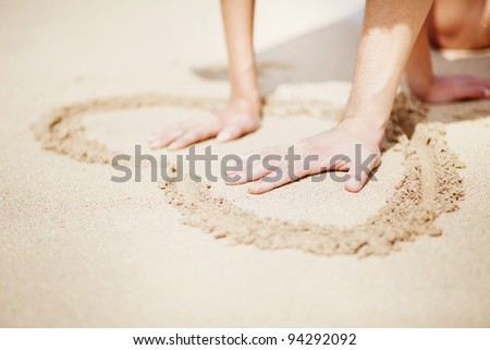 couple on the beach making heart on the sand, focus on male hand - stock photo