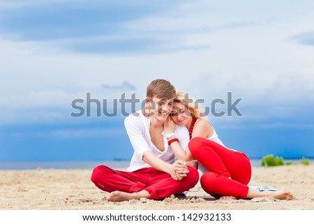 Couple on the Beach Practicing Yoga. Relaxation, meditation, healthy lifestyle. - stock photo