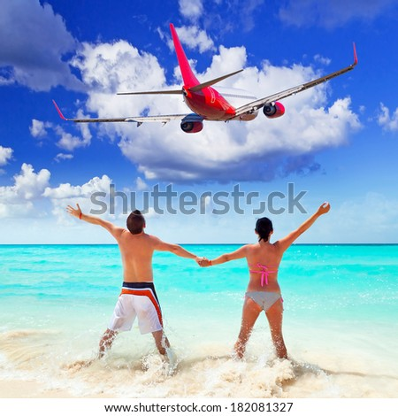 Couple on the beach watching flying aircraft - stock photo