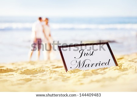 "couple on the beach with plate with ""just married"" text on it - stock photo"