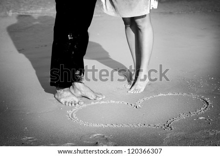 Couple on the beach with symbol of heart on the sand - stock photo