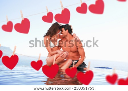 Couple on the pool edge against hearts hanging on a line - stock photo