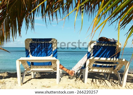 couple on the sun lounges enjoying holidays at the beach - stock photo