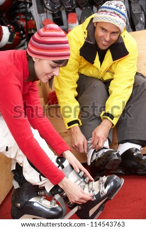 Couple On Trying On Ski Boots In Hire Shop - stock photo