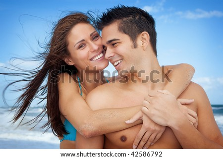 Couple on vacation at the ocean, both smiling - stock photo