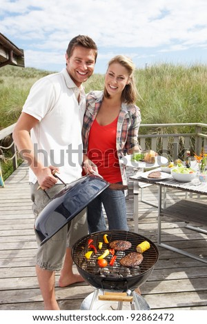 Couple on vacation having barbecue - stock photo
