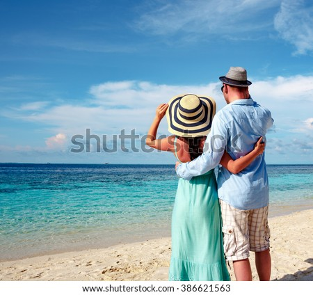 Couple on vacation walking on a tropical beach Maldives. Man and woman romantic walk on the beach. - stock photo