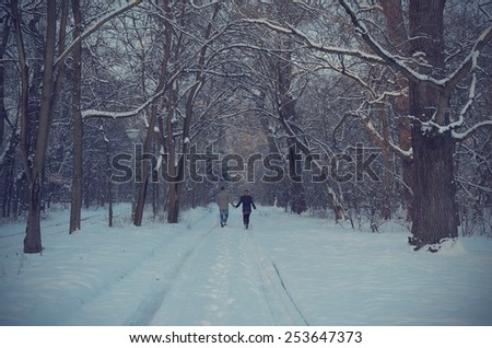 Couple on winter path in forest at night - stock photo