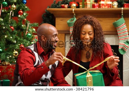 Couple opening present together by Christmas tree - stock photo