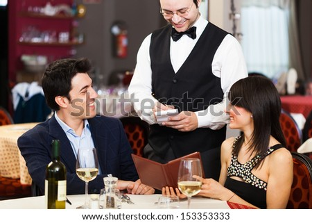 Couple ordering dinner in a restaurant - stock photo