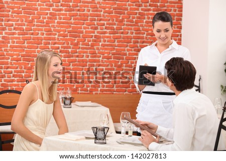Couple ordering food in restaurant - stock photo