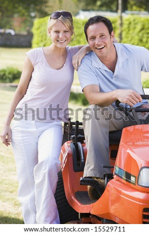 Couple outdoors with lawnmower smiling - stock photo