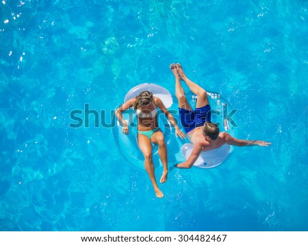 Couple Outside Relaxing In Swimming Pool in the summertime - stock photo