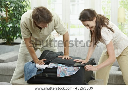 Couple packing for holiday, trying to close suitcase full with clothes. - stock photo