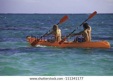 couple paddling their kayak in hawaii - stock photo
