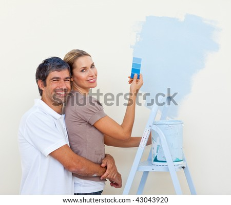 couple painting together in their new house - stock photo