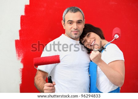 Couple painting wall red - stock photo