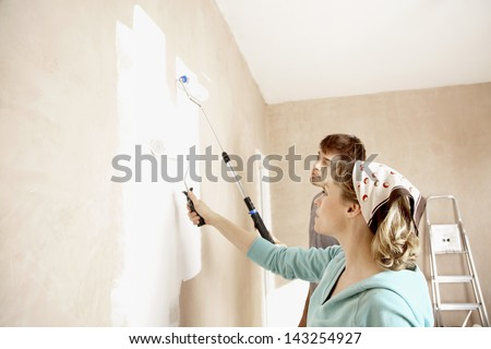Couple painting wall together with paint rollers - stock photo