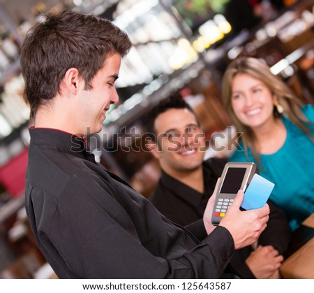 Couple paying by credit card at the restaurant - stock photo