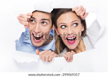 Couple peeping through hole on paper - stock photo