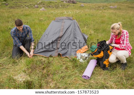 Couple pitching their tent in the countryside - stock photo