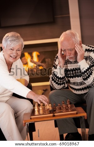 Couple playing chess in cosy living room in front of fireplace, elderly woman winning the game, senior man looking troubled.? - stock photo